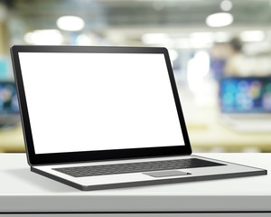 Laptop with blank screen on laminate table and blurred backgroun