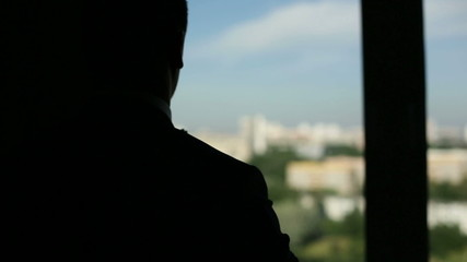 Silhouette of a man wear his jacket on the balcony