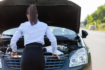 Businesswoman is looking inside the car hood