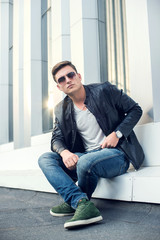 fashion man in black leather jacket, sunglasses and jeans
