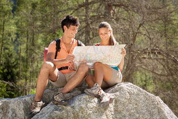 Couple is looking at the path on a map while relaxing on a big r