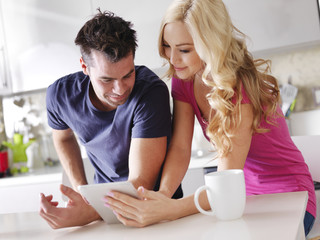 couple using tablet pc to shop online in kitchen