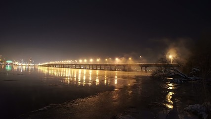 The river with illuminated bridge in winter night