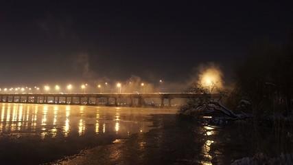 The river with illuminated half-bridge in winter night