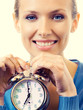Portrait of young smiling woman with alarmclock