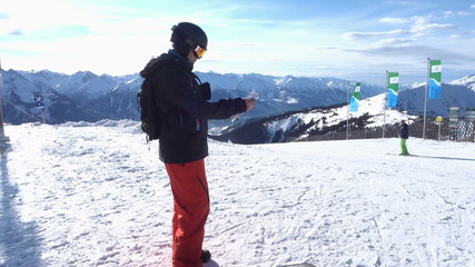 Snowboarder standing on edge of hill and read the map