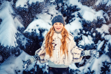 Portrait of the beautiful girl throwing snow in the winter wood