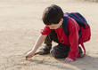 Child drawing into sand