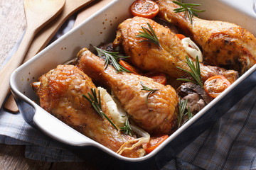 chicken legs with rosemary in a baking dish close-up horizontal