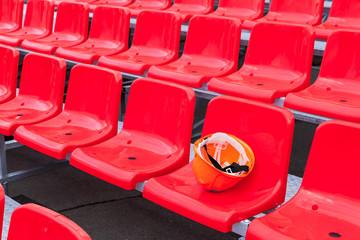 Single construction helmet lies on a plastic chair