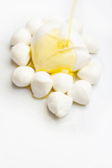 Various types of mozzarella cheese on olive oil with empty space