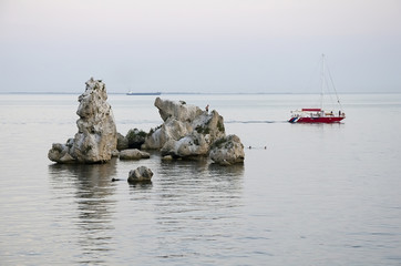 Yacht sails past the rocks in the sea