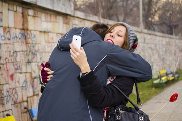 Boy hugging a girl while she looks at her smartphone