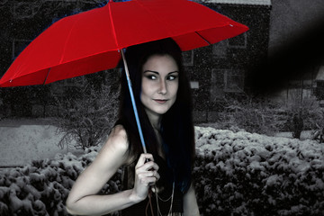 Beautiful woman with red umbrella on a winter night