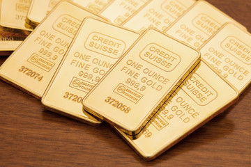 One ounce gold bars on dark wood surface