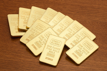 Several one ounce gold bars on wood surface