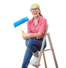 Surprised woman with paint roller sitting on ladder