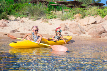 Little adorable girls enjoying kayaking on yellow kayak