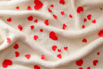 Many small red hearts on a fluffy beige plaid.