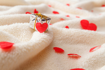 Small gift box and a lot of little red hearts on a fluffy plaid.