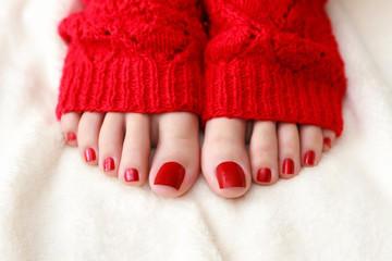 Female feet with a pedicure in red socks