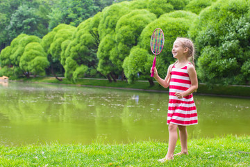 Adorable little girl playing badminton on picnic