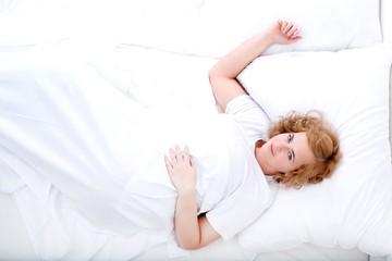 Junge, mollige Frau im Bett