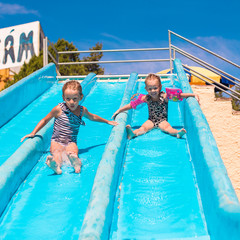 Little adorable girls at aquapark during summer vacation