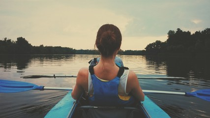 Rowing on kayak down the river on sunset