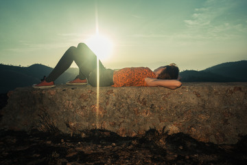 Woman lying on unusual rock at sunrise