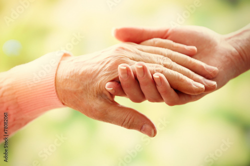 Leinwanddruck Bild Old and young holding hands on light background, closeup