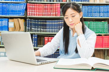 Asian student using laptop computer in college library
