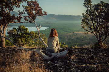 Woman sitting on a hill at sunrise