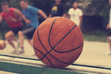 Basketball ball on a bench with defocused players.