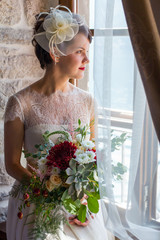 young and attractive bride sitting by the window