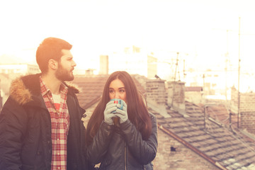 Couple enjoying outdoors with a coffee to warm up.