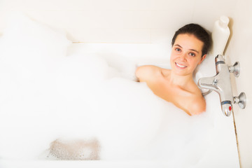 Happy  woman covered foam in bath