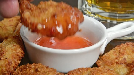 Coconut shrimp being dipped into a sweet sour cocktail sauce