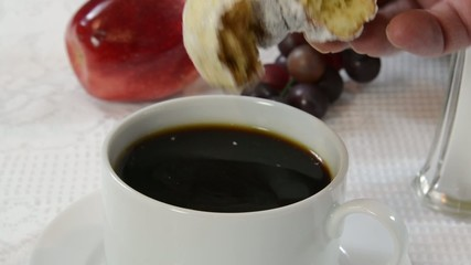Dunking a donut into a cup of black coffee