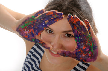 Artist looks out at her hands painted colored paint