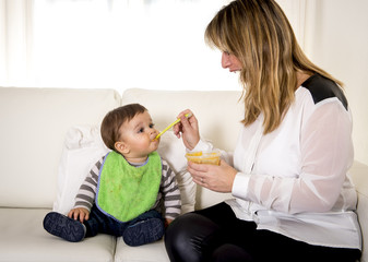 mother with spoon porridge feeding sweet baby son
