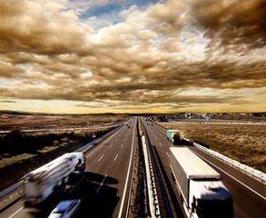 Camiones y coches en la carretera. Logística y almacenaje