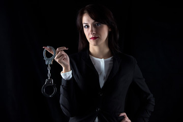 Portrait serious woman with pair of handcuffs