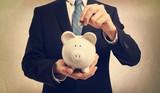 Young man depositing money in piggy bank - 78086434