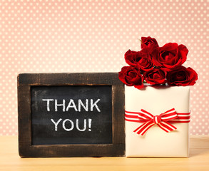 Thank you message on chalkboard with roses and present box