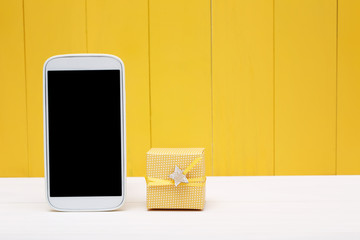 Cellphone and small gift box over yellow wood
