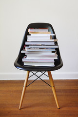 Contemporary black dining chair with stack of books