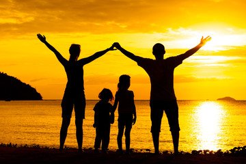 Silhouette of happy family who playing on the beach at the suns