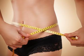 Frau überprüft Erfolg ihrer Diät mit Maßband