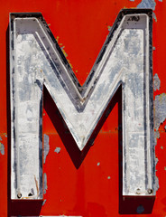 """Vintage, run-down, antique letter """"M"""" on a red background"""
